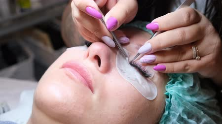 kiterjesztés : Young woman undergoing eyelash extension procedure in beauty salon, closeup. Stock mozgókép
