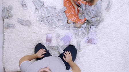 доллар : Female and male throw at each other a lot of banknotes of dollars on the bed, slow motion, top view.