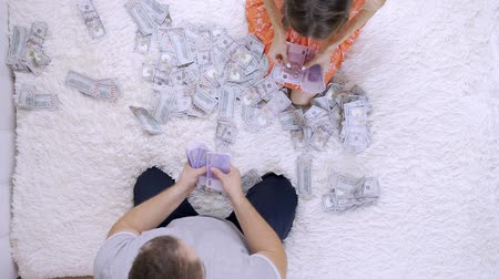 ücret : Female and male count a lot of dollar bills on the bed, slow motion, top view.