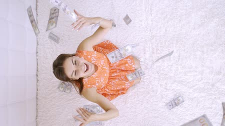 объем : large amount of money falls on a woman white bed. The girl enjoys a lot of money. slow motion. Huge wealth of money, top view.