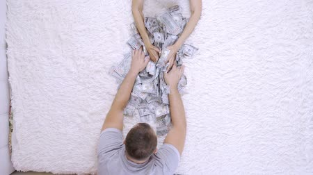 ücret : Female and male rake a lot of dollar bills on the bed, slow motion, top view.