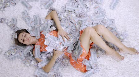 euro banknotes : Girl lies on a white bed in lot of money. The girl enjoys lot of money. slow motion. Huge wealth of money.