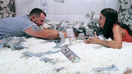 finança : Female and male rake a lot of dollar bills on the bed, slow motion, top view.