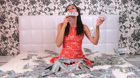 euro banknotes : large amount of money falls on a woman white bed. The girl enjoys a lot of money. slow motion. Huge wealth of money, top view.