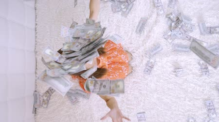 salário : large amount of money falls on a woman white bed. The girl enjoys a lot of money. slow motion. Huge wealth of money, top view.