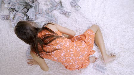 cem : Female raking lot of banknotes of dollars on the bed, lot of money, slow motion, top view. Vídeos