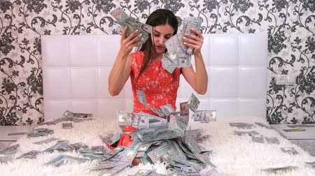 accumulation : beautiful girl enjoys tremendous wealth. female throws up a lot of banknotes on a white bed, throws money, top view. Stock Footage