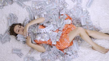 ücret : Girl lies on a white bed in lot of money. The girl enjoys lot of money. slow motion. Huge wealth of money.