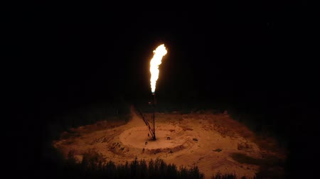 нефтехимический : huge torch of fire on in the middle of the forest at night. gas processing, environmental pollution concept, global warming.
