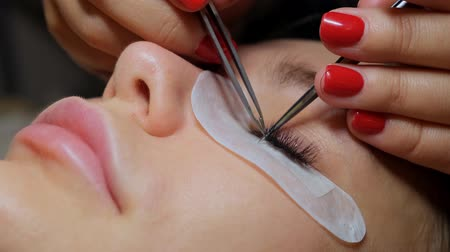 sahte : Beautiful Woman with long eyelashes in a beauty salon. Eyelash extension procedure. Lashes close up. Stok Video