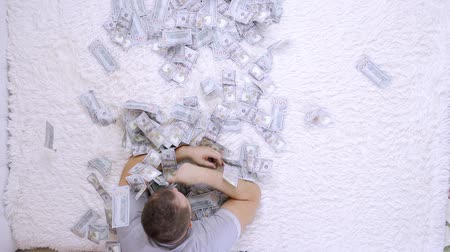 cem : Female and male throw at each other a lot of banknotes of dollars on the bed, slow motion, top view.