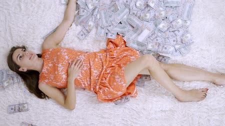 ücret : lot of banknotes fly in the air on a girl lying on a white bed in slow motion. Huge wealth of money.