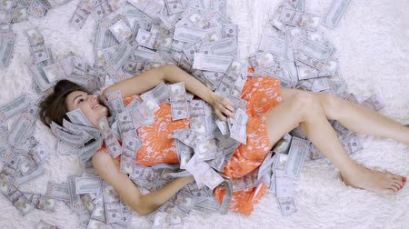 beaucoup d argent : Many banknotes fly in the air overhead in slow motion. A girl lies and a lot of money falls on her. happy woman rejoices. Huge wealth of money, slow motion, top view.