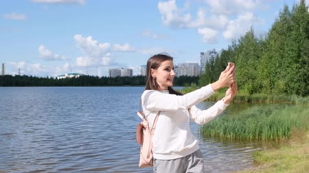sturen : Beautiful girl with a backpack takes a selfie near the lake and video call