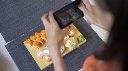 cozinha japonesa : Girl takes pictures of sushi on phone. A girl takes pictures of sushi on the phone that lie on a black table Stock Footage