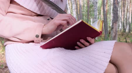 思考 : close-up shot of a girl in the autumn forest, a female hand writes with a pen in a book. A woman sits near a tree in the autumn forest and holds a book in her hands..