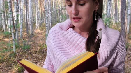 roman : close-up shot girl in the autumn forest, reads a book, a woman sits near a tree in the autumn forest and holds a book in her hands. Stok Video