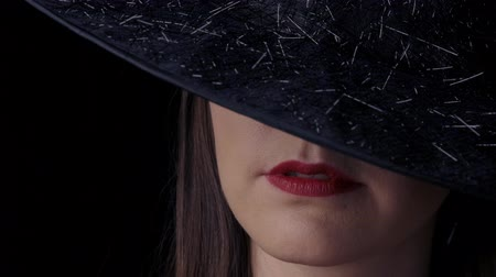 witch hat : Beautiful sexy woman in a black witch costume with red lips and a hat, looking at the camera and smiling. close-up. Stock Footage