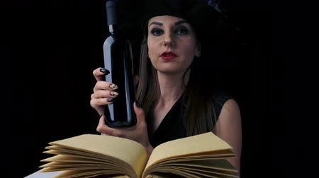 kırmızı şarap : beautiful sexy woman in a black witch costume and hat, holds a bottle of red wine in her hands, looks at the camera and smiles. close-up. Halloween holiday party