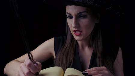 şeytan : Beautiful sexy woman in a black witch costume and hat, conjures over a book with a pen, writes a pen in a book. Halloween holiday party Stok Video