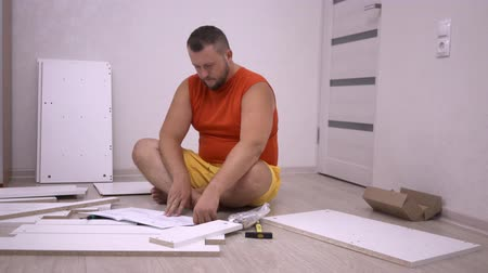 монтаж : Male collects white wooden furniture in a new house using instructions. A man collects a cabinet on his own at home Стоковые видеозаписи