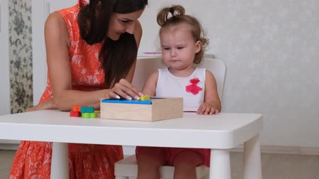 сортировать : little Daughter with mother, teacher play educational toys, lay and arrange colorful figures. Learning through experience concepts, rough and fine motor skills.