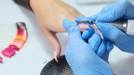 tırnak : Hardware manicure. manicurist makes hardware manicure for woman in beauty salon. master of manicure removes cuticles on nails. Slow motion. hardware manicure.