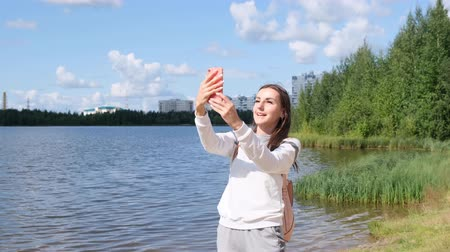 sturen : Beautiful girl with a backpack takes a selfie near the lake and talks on a cell phone on video call Stockvideo