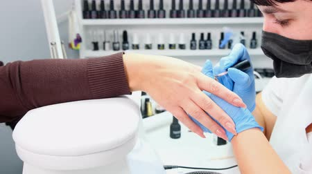 tırnak : Manicurist is applying gel polish to the nails of a client in a beauty salon. Build up nails. Manicure.