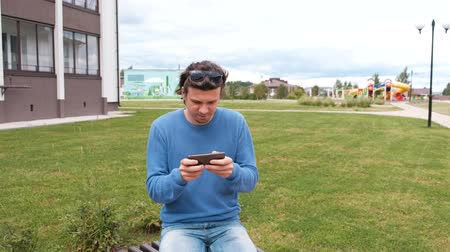 pálido : Man is playing a game on mobile phone sitting on bench near the home. Vídeos