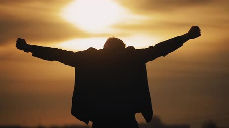 Man raises his hands at sunset worship or freedom theme