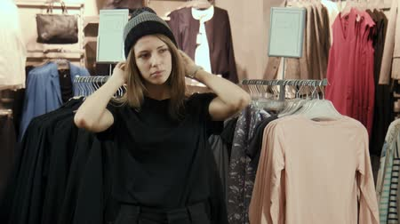 gündelik kıyafetler : The girl the teenager tries on a cap in a store