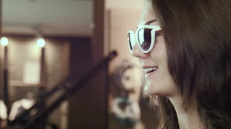 espetáculos : The girl tries on sunglasses in shop Stock Footage