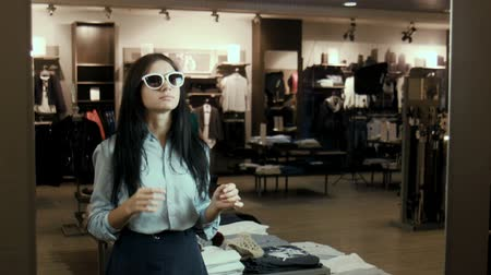 optyk : The ridiculous girl tries on sunglasses in a store