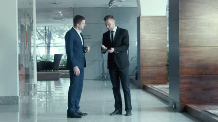 консалтинг : Communication of two businessmen. One shows another on the touchpad