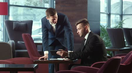 paylaşımı : The businessman explains the business plan and shows to the interlocutor on the touchpad