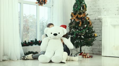 přítomný : Two teen girl hiding behind the christmas bear and smiling at the camera
