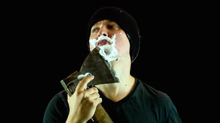 barbear : the man in a cap has a shave with an axe, black background Vídeos