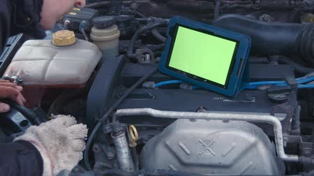 rész : The man looks in the touchpad with greenscreen and checks the engine in the car Stock mozgókép