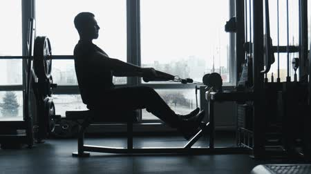vállalkozó : The guy does exercises on the exercise machine in the gym
