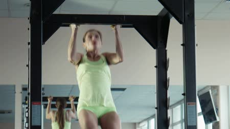 behind bars : The girl pulling up on a horizontal bar in a gym, close shot Stock Footage