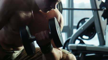 борода : The bodybuilder does exercise for a bitseps of dumbbells