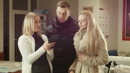 мебель : The seller advises a couple using the touchpad in shop