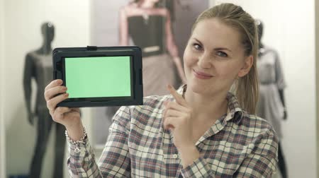 clientes : The girl shows the tablet with the green screen in store