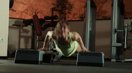 gymnasta : The woman does fitness exercise push-ups on fitness steps in gym