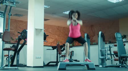 tornaterem : Young girl doing squats and jumps in fitness gym