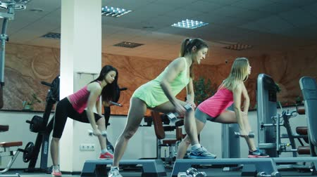 атлетика : Three females doing exercises with dumbbells in gym Стоковые видеозаписи