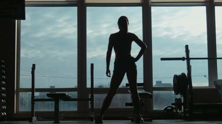 saudação : Silhouette of the attractive woman going on a fitness studio to a window, shooting in the movement