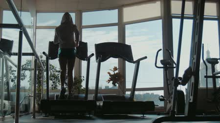buty sportowe : Attractive woman running on treadmill in sport gym, sport life and sport equipment, wide shot Wideo