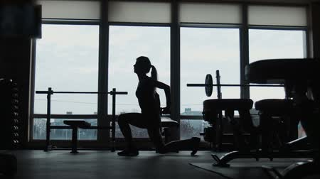 tornaterem : The silhouette of the young girl does fitness workout near window, wide shot Stock mozgókép